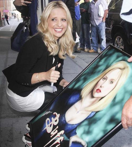 سارة ميشيل غيلير توقع على صورة لها رسمها أحد معجبيها تحمل شخصيتها في مسلسلها الشهير buffy the vampire slayer في نيويورك الاثنين